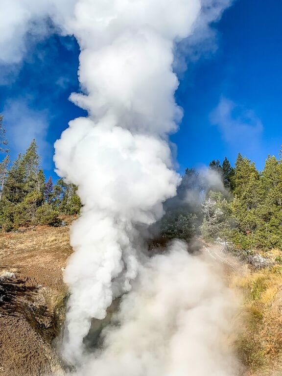 Dragon mouth spring spurting dense pressurized steam into the sky