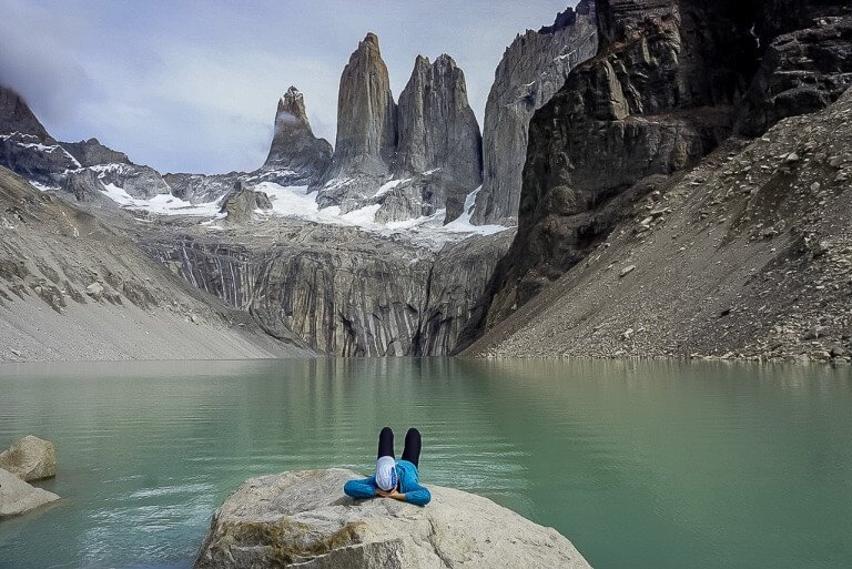 Kristen laying on a boulder in front of Torres del Paine laguna enjoying the hike