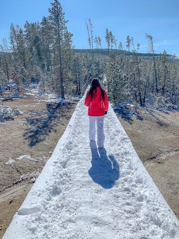 Kristen walking on snowy boardwalk Norris Geyser Basin Yellowstone