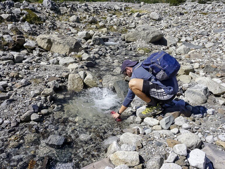 Mark filling water bottle up in a mountain river W Trek Chile hiking tips for beginners