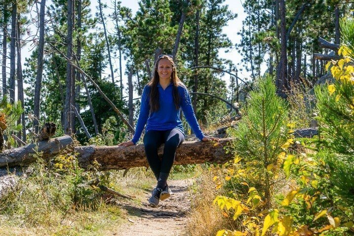 Kristen sat on a log in South Dakota Black Hills National Forest