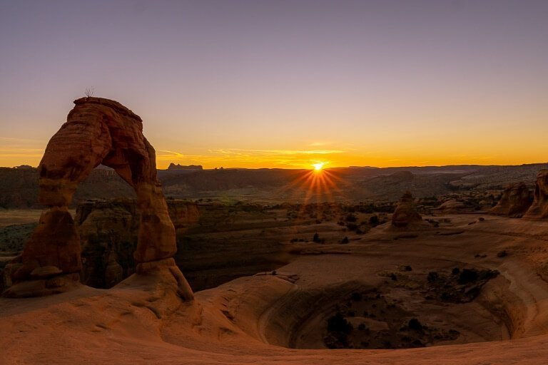Sunset over Delicate Arch and bowl sun setting in horizon deep orange and purple sky
