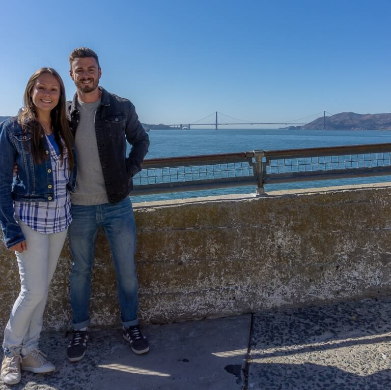 Mark and Kristen on Alcatraz Island after tour walking around grounds golden gate bridge in background across San Francisco bay