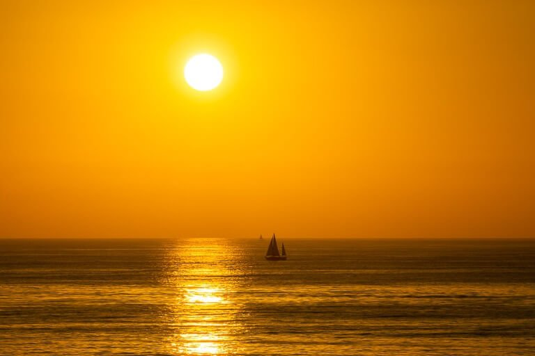 Sunset cliffs in San Diego watching the sun set in an orange sky with sail boats out at sea