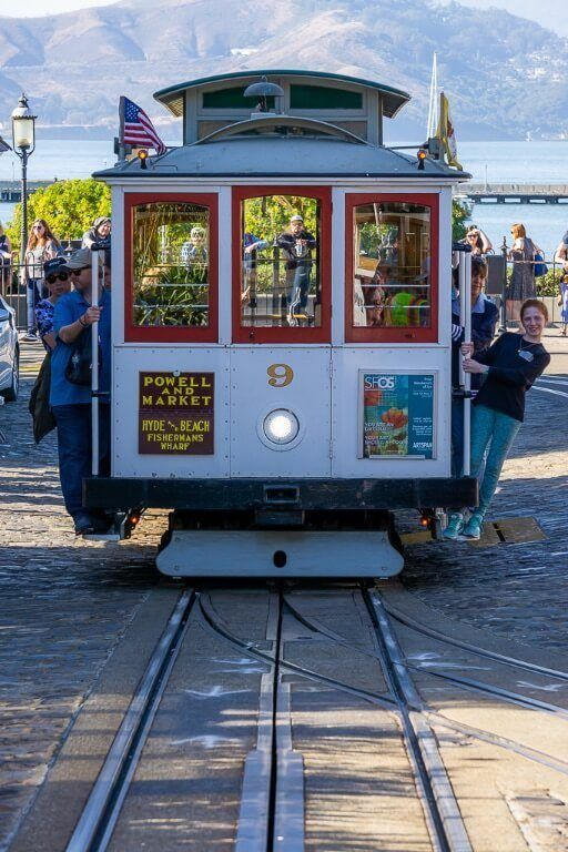 Iconic San Francisco cable car from the front and people hanging out must visit on sf itinerary