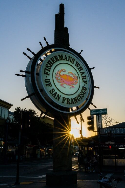 Explore touristy fisherman's wharf as part of your first time visit to San Francisco itinerary sign lit up and sunburst