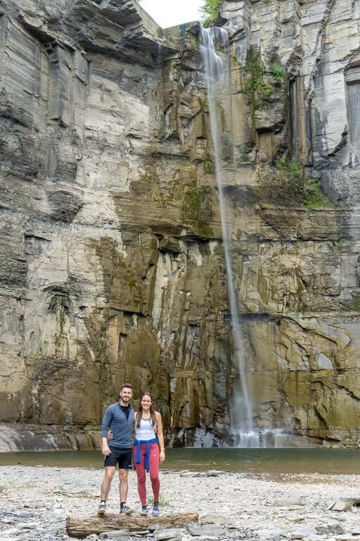 Mark and Kristen stood on a log in front of towering Taughannock Falls waterfall Ithaca NY state park