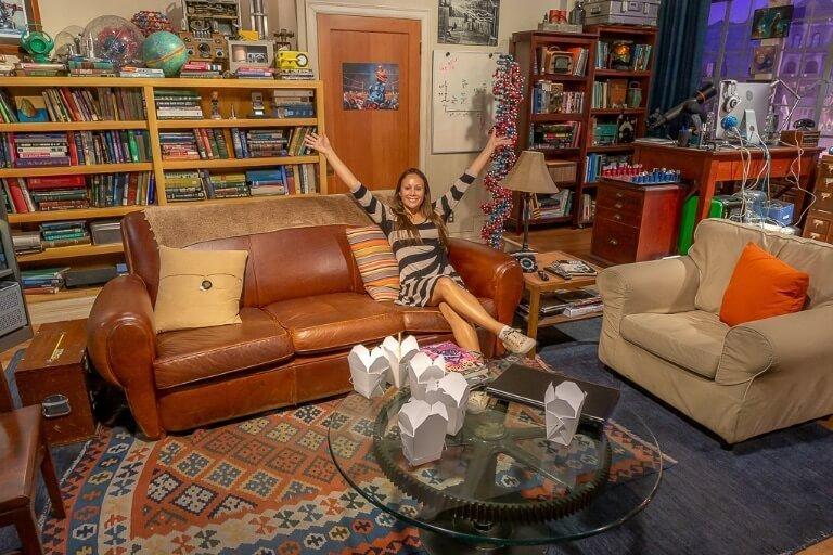 Kristen sitting on sofa of Big Bang theory apartment set