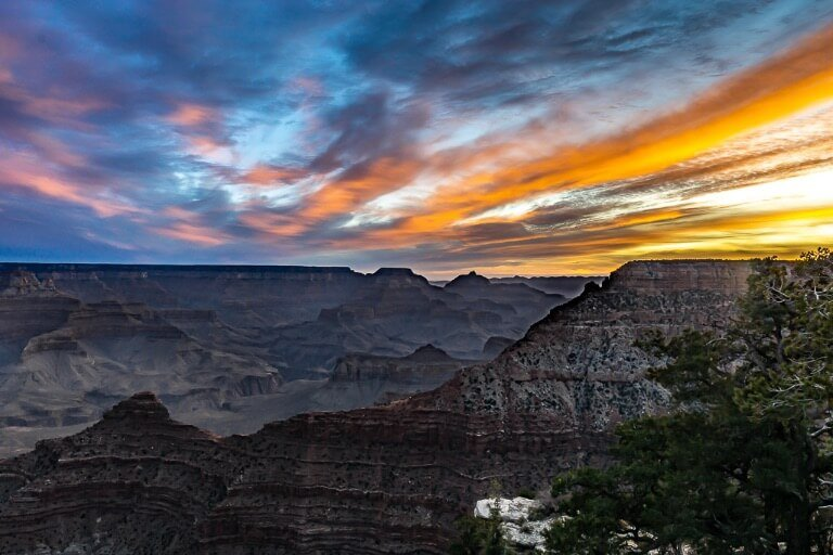 Epic sunrise from Mather Point in Grand Canyon South Rim beautifully vibrant morning colors lighting the sky up over canyon formations best way to start one day at the national park
