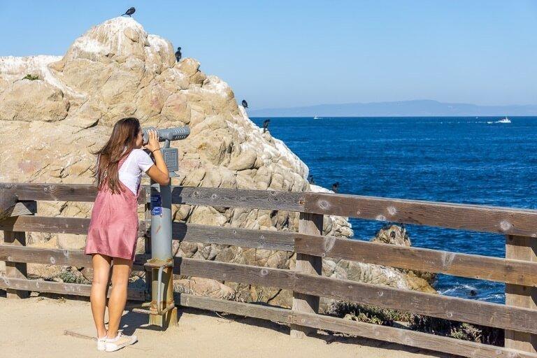 Kristen looking through a telescope near Monterey Bay California when driving San Francisco to San Diego pacific coast highway 1