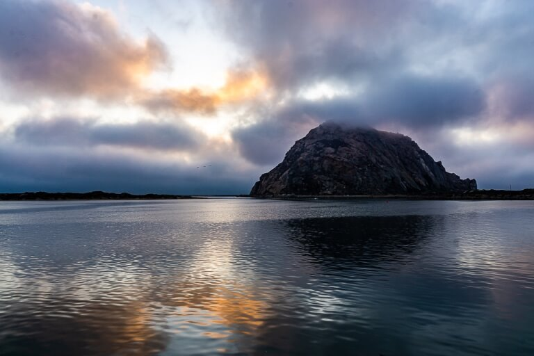Morro Bay is an intriguing town between San Francisco and Los Angeles huge random rock at sea with colors in sky