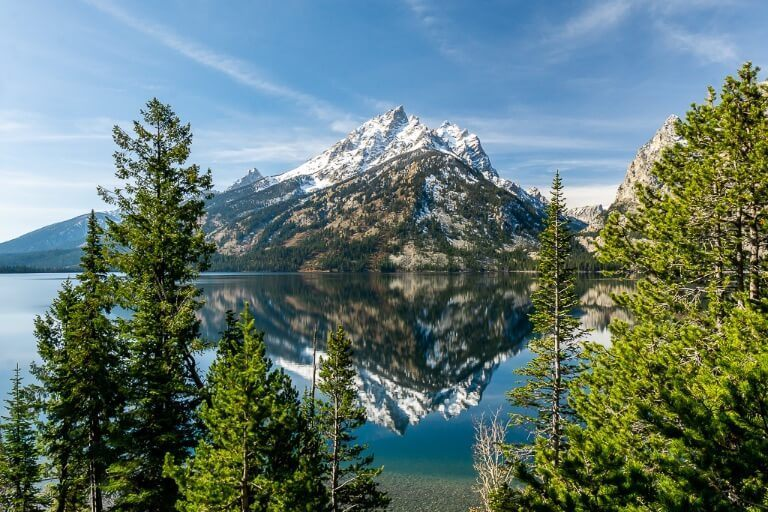 Incredibly beautiful mountain reflection in Jenny Lake between pine trees at Grand Teton National Park best things to do itinerary and photography locations